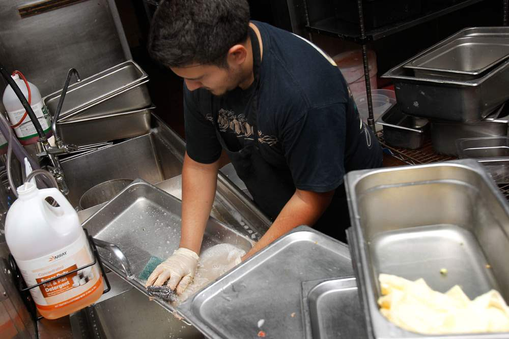 Antonio-Vasquez-cleans-dishes-in-the-kitchen-of-El-Vaquero