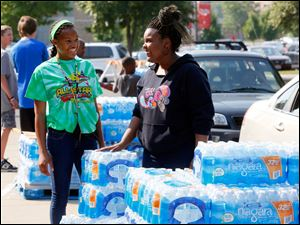 Volunteers Dakari Parish, left, 13, and Ayanna Bishop, right, 17, hand out free water in the receiving area at Central Catholic High School.