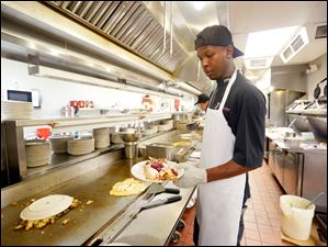 Chef T.J. Harvey, at The Original Pancake House, puts the finishing touches on crepes while cooking for the lunch crowd. Last night they decided to make their batters with bottled water.