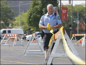 Toledo Police Officer J. Middleton breaks down the barriers and tape at 11:00 a.m. when water distribution at Central Catholic was closed.