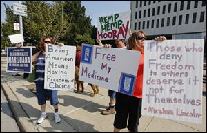 Linda Turvey, left, Eddie Currier, back, center, and wife Heather Currier, of Northwest Ohio NORML, demonstrate outside One Government Center in Toledo today. The group presented petitions to Toledo City Council proposing an ordinance for the decriminalization of marijuana.