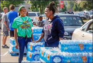 Volunteers Dakari Parish, left, 13, and Ayanna Bishop, right, 17, hand out free water in the receiving area at Central Catholic on Monday despite the all-clear declaration issued by Mayor Collins and other officials.