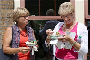 Terri Seagert, of Waterville, left, jokes with Kathy Isola, of Indianapolis, right, over a sample of Garbage Salad outside Grumpy's.