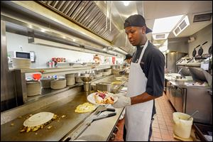 Chef T.J. Harvey, a worker at the Original Pancake House, puts the finishing touches on crepes during the lunch rush on Monday. The restaurant was closed both Saturday and Sunday. '‍We were probably in the thousands of dollars lost. It was pretty bad,' said Candie Hayes, the restaurant's manager.