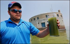 Shane Gaghen of Oregon holds a glass of algae filled Lake Erie water near the Toledo water intake crib on Sunday. The National Wildlife Federation conducted a media boat tour of the area.