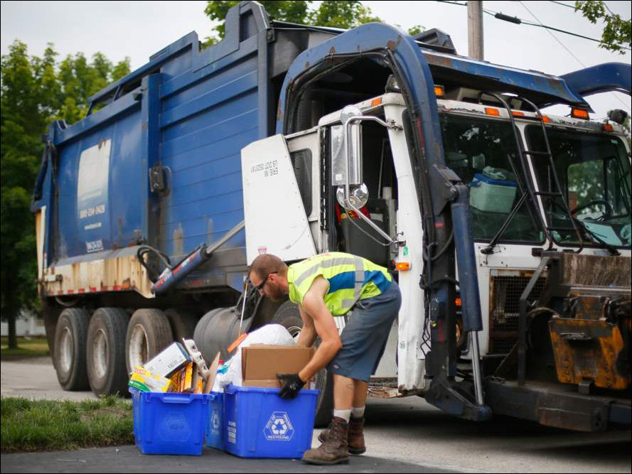 Bryan Shipman, with Republic Services, empties a recycling bin on Duane St. near W. Wayne St. in Maumee.