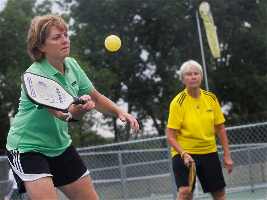 Marsha Koch, left, returns the ball.