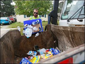 Bryan Shipman, with Republic Services, empties a recycling bin on W. Broadway in Maumee.