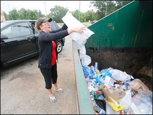 Jessica Calevro recycles a large bag of water bottles at the recycling area behind Kroger on  7545 Sylvania Ave.