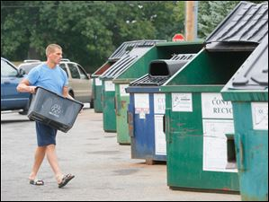 Ryan Fox recycles a large bin of water bottles at the recycling area behind Kroger on  7545 Sylvania Ave.
