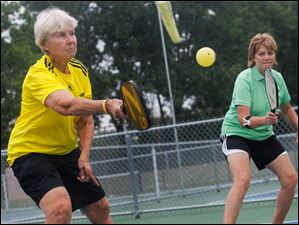 Connie Mierzejewski, left, returns the ball as she plays a match with Marsha Koch.