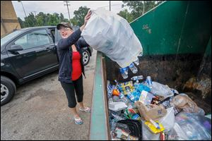 Jessica Calevro recycles a large bag of water bottles at the recycling area behind Kroger on 7545 Sylvania Ave. near King Road.