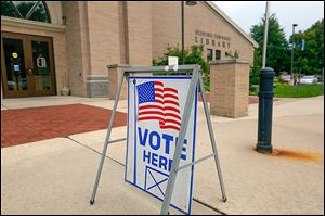 A sign in front of the Bedford Branch Library identifies it as a polling station for the Michigan primary Tuesday.