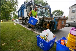 Bryan Shipman, with Republic Services, empties a recycling bin on West Broadway in Maumee.