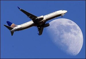 A United Airlines jet approaching Los Angeles International Airport passes in front of a Waxing Gibbous moon on July 17.