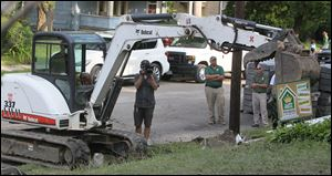 LeBron James operates an excavator as a camera operator and Darren Rowland and Brian Rice of Rice Nursery and Landscaping, look on.