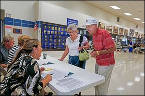 Precinct 5 voters Dorothy, left, and Frank Konwinski sign in to vote at Springfield High School with poll workers, from  left, Paul and Lynne Philibin of Monclova Township and Linda Kulwicki of Toledo.