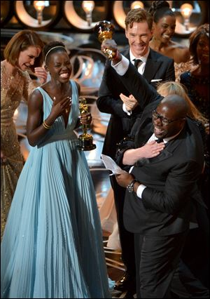 Actress Lupita Nyong'o, left, and director Steve McQueen celebrate onstage as they accept the award for best picture of the year for '‍12 Years a Slave' during the 2013 Oscars.