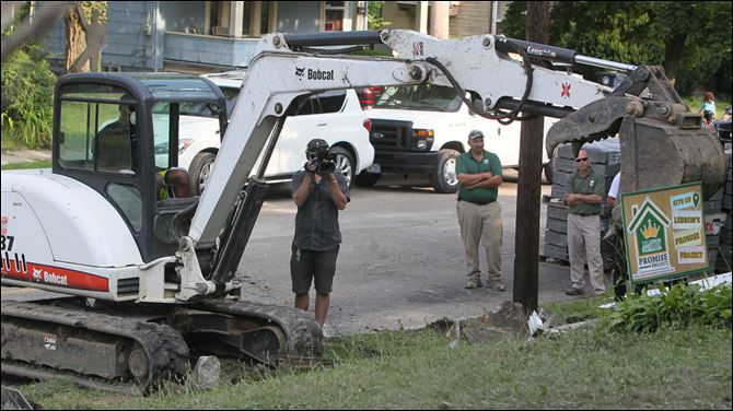 LeBron Rehabbing homes LeBron James operates an excavator as a camera operator and Darren Rowland and Brian Rice of Rice Nursery and Landscaping, look on.