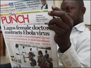 A man reads a local newspaper with headline news about a Lagos female doctor contracts Ebola Virus, in Lagos, Nigeria, Tuesday.