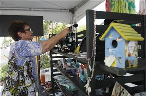 A shopper admires jewelry created by the Toledo School for the Arts students at last year's Levis Commons Fine Art Fair in Perrysburg.
