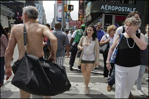 Pedestrians react as George Davis, left, walks nude through Times Square, Wednesday, Aug. 6, 2014, in New York. Davis, a candidate for the San Francisco Board of Supervisors, gave a speech in the nude speaking out against a 2013 San Francisco public nudity ban.