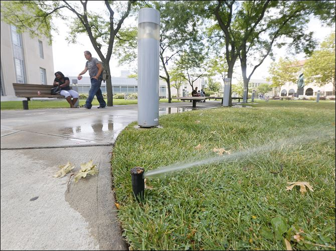 n5sprinkler-2 Sprinklers water the lawn at the Main Toledo-Lucas County Library downtown on Wednesday.