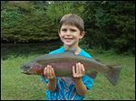 David Johnson, age 7, with a rainbow trout he caught on Cold Creek at the Castalia State Fish Hatchery property.