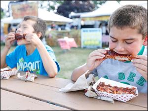 Devan Mathias, 10, Toledo, left, and Tommy Mechling, 10, MAumee, enjoy ribs from Deet's BBQ.