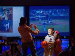 Jacqueline Martinez takes a picture of her son Ryan, 6, and daughter Isabel, 4, at Lucky Strike in Chicago. The number of U.S. bowling alleys has fallen fron 10,000 in the early 1980s to about 4,500.