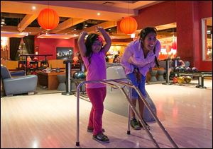Jacqueline Martinez and her daughter Isabel, 4, watch the progress of a ball down the lane at Lucky Strike in Chicago. While 69 million Americans still bowl at least once a year, league play has made a dramatic decline.
