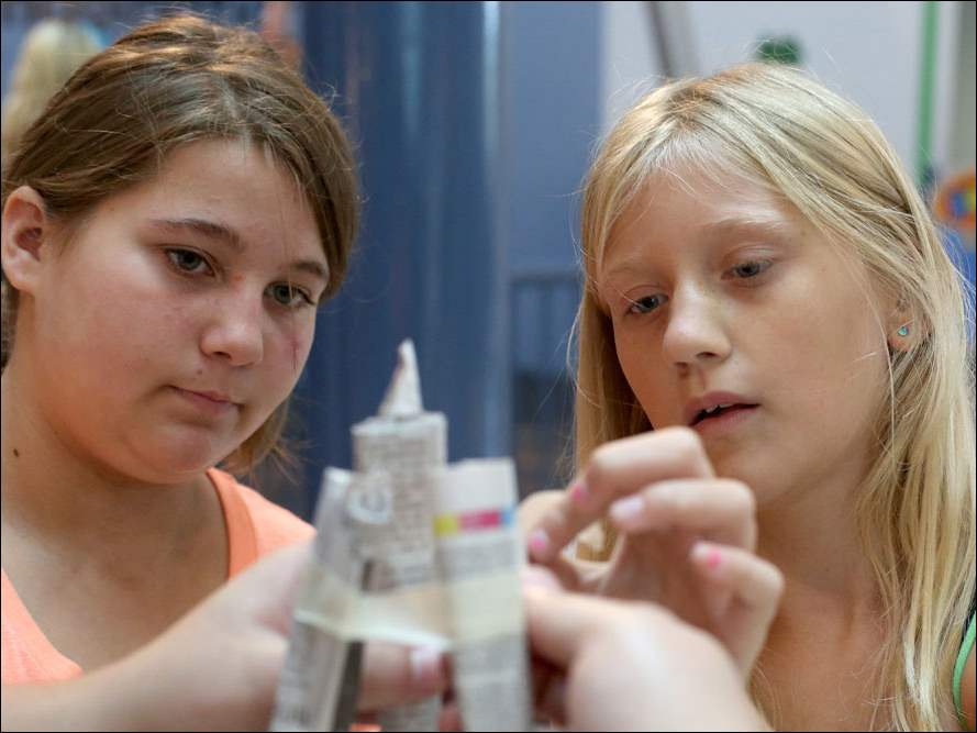 Cousins Brandi Smith, 11, left, and Madison Kruse, 11, of Swanton, put the finishing touches on their paper tower.