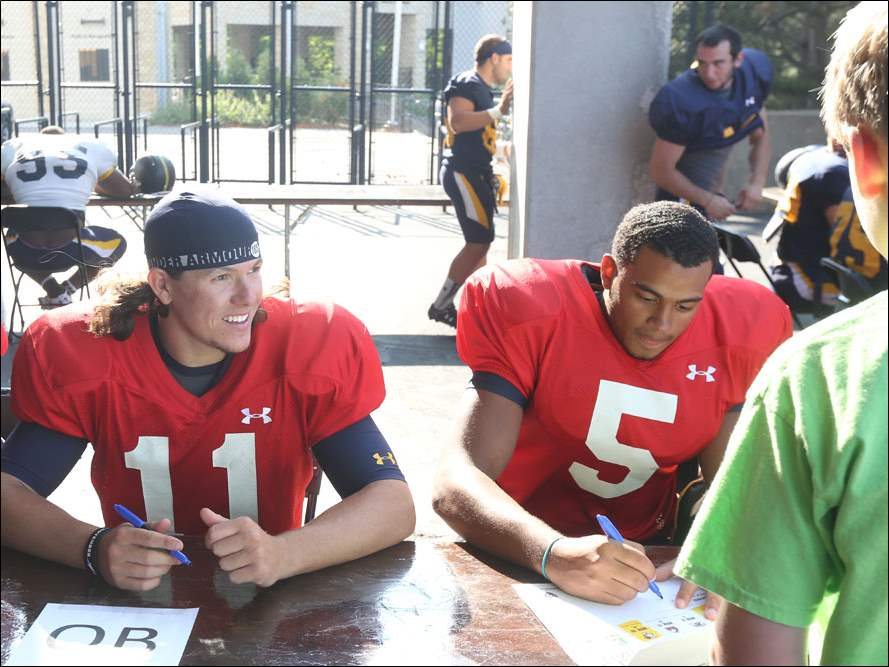 Quarterbacks Logan Woodside, left, and Michael Julian, right, sign posters and greet fans.