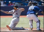 Detroit Tigers' Miguel Cabrera, left, slides safely past Toronto Blue Jays catcher Dioner Navarro to score on Victor Martinez's two-RBI double.