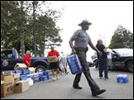 Sgt. Chris Fitzgerald, center, and other police officers and volunteers load water into citizens' cars at Waite High School.