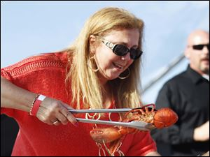 Diana Dettman picks up a lobster to put on her plate at the Toledo Chamber Clam Bake held at Hollywood Casino.