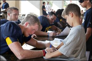 University of Toledo tight end Grant Sherman signs the T-shirt of 8-year-old Leyton Marsh during Fan Appreciation Day on Saturday at the Glass Bowl.