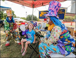 Nevaeh Cooper, 4, of Northwood, center, thanks Happy the Clown (Matthew Onweller of Swanton), right, for her balloon princess as Laffy the Clown (Chase Tressler of Swanton) watches.