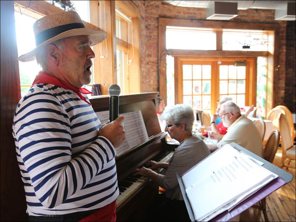 Dave Herring sings as JoAnn McKelvey plays the piano during a fund-raiser for the Most Blessed Sacrament Choir Sunday at Manhattan's in Toledo.