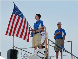 Cody Crowther of Sylvania, left, holds the U.S. flag during the playing of the national anthem. Behind him are race announcer Bob Wombold, mostly obscured, and race director Jim Donaldson, right.