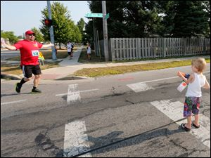 A runner welcomes a squirt from 5-year-old Izzaik Gullett of Fremont, right.