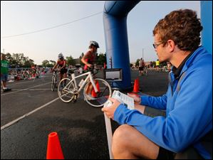 Jeff Roberts of Grand Rapids, Mich., right, enters the bicyclists' numbers as they begin that segment of the race.