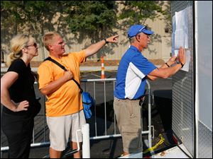 Dawn, left, and Todd Williams of Fremont look for their son's results as race director Jim Donaldson puts them up.