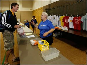 Rob Jankowski of Plymouth, Mich., left, picks up his race packet from Connie Ayres, of Petersburg, Mich.