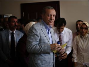 Prime Minister Recep Tayyip Erdogan, who is the front-runner in Turkey's presidential election, holds his ballot paper at a polling station Sunday in Istanbul, Turkey.