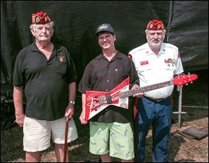 Mike Mori, director of sales for The Blade, flanked by Ronald Schramm, left, and Bob Baker of the Blue Diamonds Detachment, Marine Corps League, holds a guitar signed by Dennis DeYoung of Styx and the group War. The guitar was raffled off during the rib-off to raise money for the Marine Corps League.