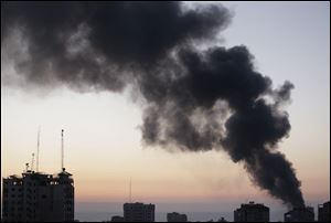 Smoke from a fire on a cleaning materials factory caused by an Israeli strike rises over Gaza City on Sunday.