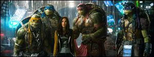 "From left, Michelangelo, Leonardo, Megan Fox as April O'Neil, Raphael, and Donatello in a scene from ""Teenage Mutant Ninja Turtles."" Paramount Pictures' comic-book adaptation featuring Megan Fox alongside computer-generated renditions of the pizza-eating, sewer-dwelling superheroes lunged into first place in its debut weekend, according to studio estimates Sunday. The action film's totally tubular result prompted the studio to announce plans Sunday for a sequel set for June 3, 2016."