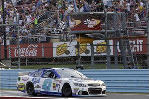 AJ Allmendinger takes the checkered flag to win a NASCAR Sprint Cup Series auto race at Watkins Glen International on Sunday in Watkins Glen N.Y.