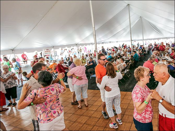 n2polish-7 People dance in the packed tent during the second annual Polka Party Picnic at St. Hyacinth Catholic Church in Toledo. Plans to raise funds for a new community center were announced at the festival.